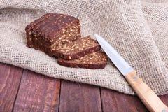 被分类的新鲜面包、在老木桌上隔绝的切片和刀子 库存图片