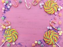 被分类的糖果和棒棒糖在桃红色木桌上 免版税库存图片