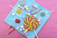 被分类的糖果和棒棒糖在桃红色木桌上 库存图片