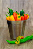 被分类的胡椒和辣椒在金属用桶提与水滴垂直格式 库存图片
