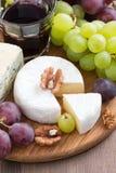 被分类的软干酪和新鲜的葡萄在一个木板 免版税库存照片