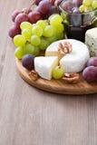 被分类的软干酪和新鲜的葡萄在木背景 库存照片