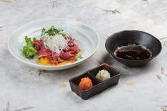 被切的半生半熟wagyu顶部用切的萝卜和薤服务与剁碎萝卜、红萝卜和Ponzu调味汁在washi 免版税库存图片