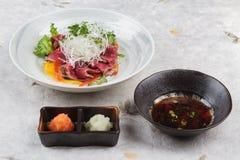 被切的半生半熟wagyu顶部用切的萝卜和薤服务与剁碎萝卜、红萝卜和Ponzu调味汁在washi 库存图片