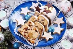 被切的圣诞节stollen在蓝色板材的蛋糕 免版税库存照片
