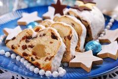 被切的圣诞节stollen在蓝色板材的蛋糕 免版税库存图片
