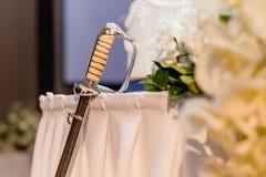 被切的婚宴喜饼的,婚礼辅助部件工具剑,我们 免版税库存照片