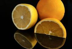 被切的柠檬和桔子在黑暗的背景与反射 库存照片