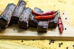 被切的烤猪肉肋骨用在委员会的红辣椒 库存照片