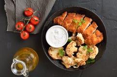 被切的烤鸡鸡胸脯和油煎的花椰菜 库存照片