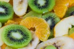 被切的猕猴桃和桔子特写镜头在水果沙拉背景 免版税库存图片