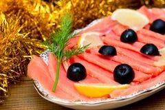被切的红色鱼三文鱼绿化在板材,木棕色背景,顶视图,食物服务的柠檬黑橄榄 图库摄影