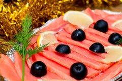 被切的红色鱼三文鱼绿化在板材,木棕色背景,顶视图,食物服务的柠檬黑橄榄 库存照片