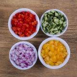 被切的菜的分类 胡椒、蕃茄、黄瓜和葱在碗 免版税图库摄影