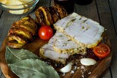被切的里脊肉烤箱片断烘烤了猪肉用油煎的螺旋土豆、蕃茄、大蒜和香料与盐 免版税库存照片
