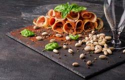 被切的jamon和空的玻璃在黑桌背景 盐味的开心果和新鲜的蓬蒿餐馆快餐的 免版税库存图片