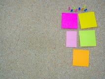 被别住的小组图钉和关于黄柏板的纸笔记 免版税库存图片