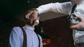 被刺字的理发师由在他的被刺字的客户的面孔,在20世纪30年代黑手党样式的理发店的剃须刷应用泡沫,刮 影视素材