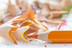 被削尖的橙色铅笔和刨花 图库摄影