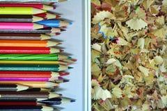 被削尖的颜色铅笔和铅笔削片在箱子 库存图片