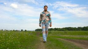 被剥去的牛仔裤的一个英俊的人在单独领域附近走 影视素材