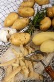 被剥皮的土豆和土豆果皮在一个木板 库存图片