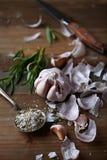 被剥皮的大蒜电灯泡、罗斯玛丽和盐在厨房用桌上 免版税库存照片