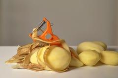 被剥皮的未加工的土豆,剥土豆和一台削皮器在一个白色背景特写镜头 免版税图库摄影