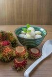 被剥皮的红毛丹充塞用在糖浆的菠萝 库存照片