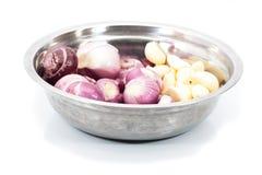 被剥皮的红色青葱和大蒜在不锈钢碗 库存图片