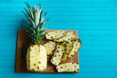 被剥皮的菠萝、果皮和刀子在绿松石木背景,拷贝空间 图库摄影