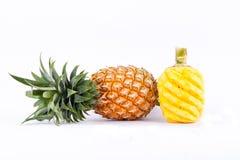 被剥皮的菠萝和新鲜的成熟菠萝在白色被隔绝的背景健康菠萝果子食物 免版税库存图片