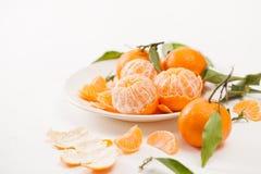 被剥皮的蜜桔和果皮与叶子在白色背景 免版税图库摄影