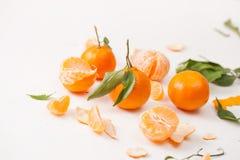 被剥皮的蜜桔和果皮与叶子在白色背景 库存照片