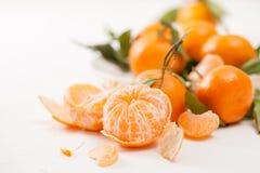 被剥皮的蜜桔和果皮与叶子在白色背景 库存图片