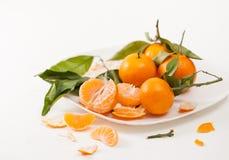 被剥皮的蜜桔和果皮与叶子在白色背景 免版税库存图片