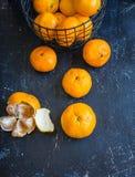 被剥皮的蜜桔桔子和蜜桔桔子在铁丝网筐在黑暗的背景 库存照片