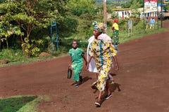 被剥皮的非洲人民、跨步在农村路的妇女和孩子 免版税库存图片
