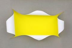 被剥去的孔在黄色背景的灰色纸 免版税库存照片