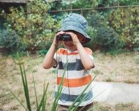 被剥离的看通过双筒望远镜的T恤杉和帽子的逗人喜爱的白种人男孩 库存照片