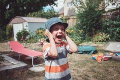戴被剥离的T恤杉和帽子有滑稽的面孔表示的男孩外面在房子后院在夏日,哭泣的尖叫 免版税库存照片