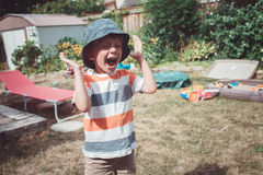 戴被剥离的T恤杉和帽子有滑稽的面孔表示的男孩外面在房子后院在夏日,哭泣的尖叫 库存照片