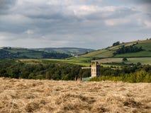 被割的干草的领域与上升在背景中的教会尖顶的 免版税库存照片