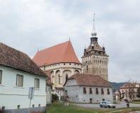 被加强的教会圣斯蒂芬和站立在路的钟楼穿过Saschiz村庄在罗马尼亚 库存照片