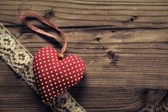 被加点的织品心脏有鞋带木头背景 免版税图库摄影