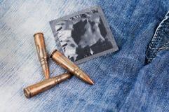 被包装的避孕套和三金属化攻击步枪的子弹在蓝色牛仔裤 库存照片