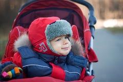 被包裹的男婴红色婴儿推车 免版税库存图片