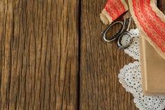被包裹的礼物、丝带和剪刀在木板条 库存图片