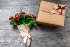 被包裹的礼物在一个木灰色背景,情人节,浪漫照片,与心脏的浪漫花束和礼物,适用于副词 免版税库存照片