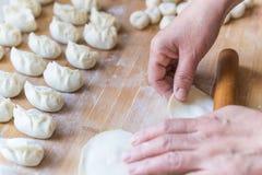 被包裹的饺子的制造过程滚动了饺子皮肤 免版税库存图片